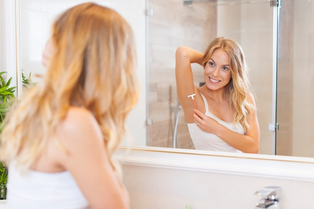 Woman shaving armpit in front of mirror