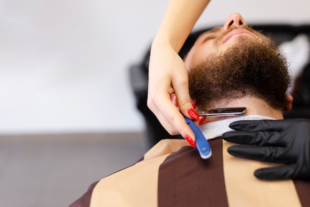 Woman shaving a client's beard with copy space