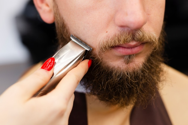 Woman shaving her client's beard close-up