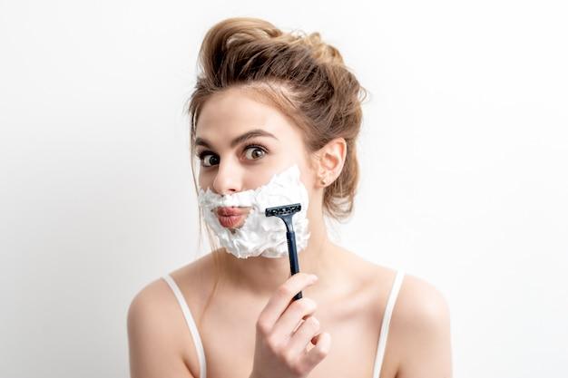 Женщина бреет лицо бритвой