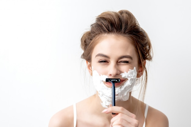 Woman shaving her face by razor