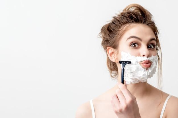 かみそりで顔を剃る女性