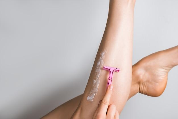 ピンクのかみそりで彼女の足を剃る女性