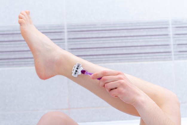 Woman shaving legs in the bathroom using razor close up. beauty treatments at home