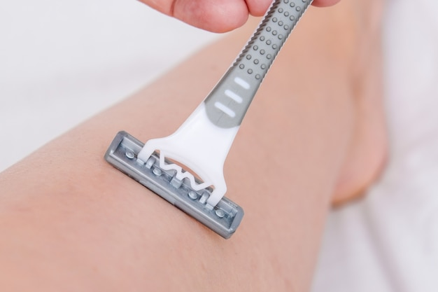 회색 일회용 플라스틱 면도기로 다리를 면도하는 여성이 원치 않는 제모를 닫습니다.
