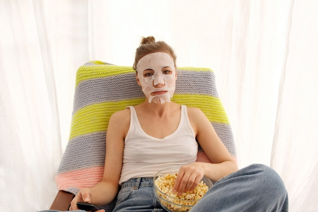 Woman in sheet mask watching tv while eating popcorn in bright room