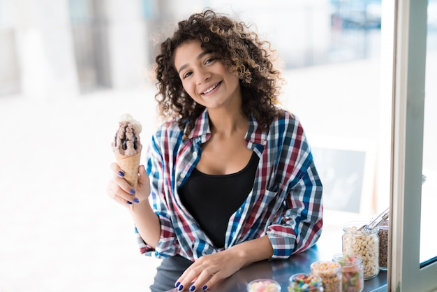 Woman in shirt buying ice cream in food truck.