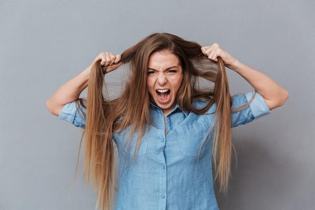 Donna in camicia che tiene i suoi capelli