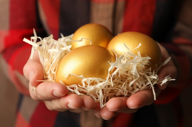 Woman in shirt holds nest with golden eggs