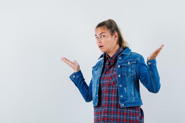 Donna in camicia, giacca che mostra gesto impotente e che sembra confusa, vista frontale.