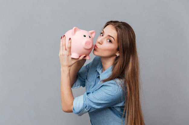 Woman in shirt kissing piggy bank