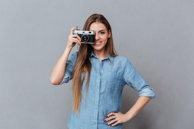 Woman in shirt making photo on retro camera