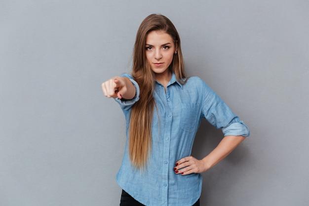 Woman in shirt pointing at camera