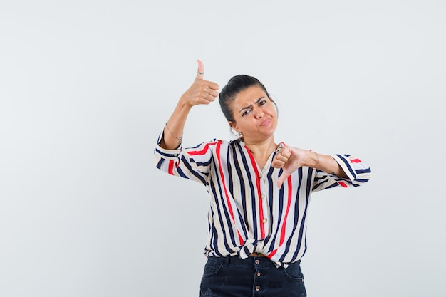 Woman in shirt, skirt showing thumbs up and down and looking indecisive