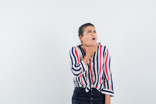 Woman in shirt, skirt suffering from sore throat and looking sick
