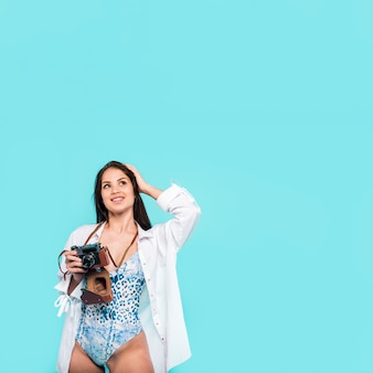 Woman in shirt and swimsuit standing and holding camera in hand