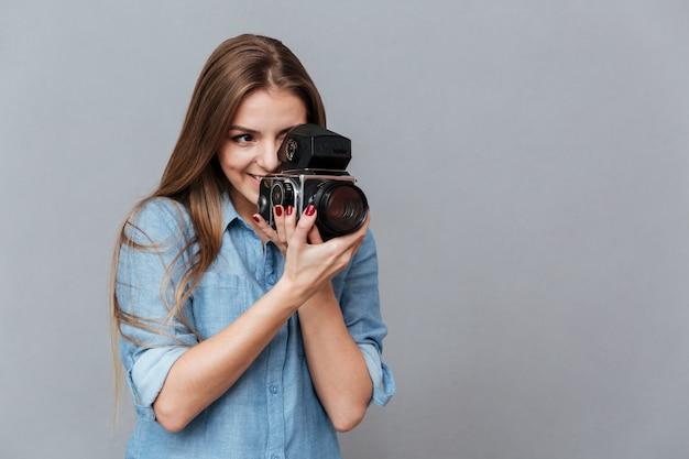 Woman in shirt using retro video camera