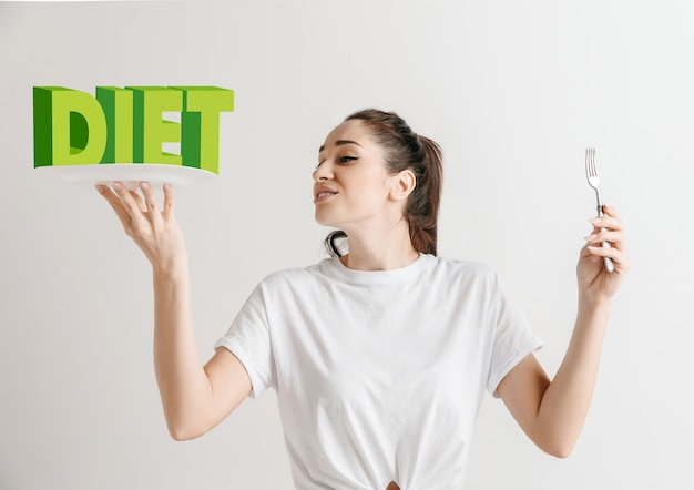 Woman in shirt with the folk isolated on white. female model holding a plate with letters of word diet. choosing healthy eating, diet, organic nutrition and nature friendy lifestyle.
