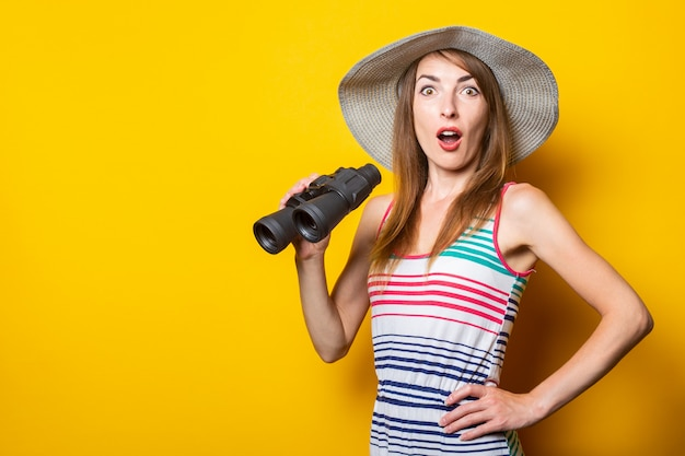 Woman in shock, surprised, in a hat and striped dress holds binoculars on a yellow space.