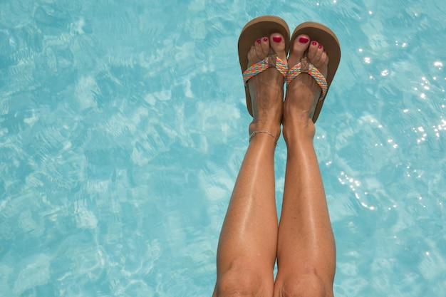편안한 수영장에 여자 신발과 다리