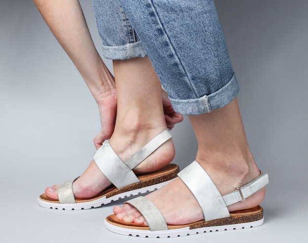 Woman shoes stylish leather sandals on her foot on white