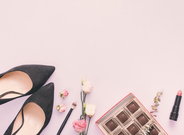 Woman shoes with cosmetics and roses on table