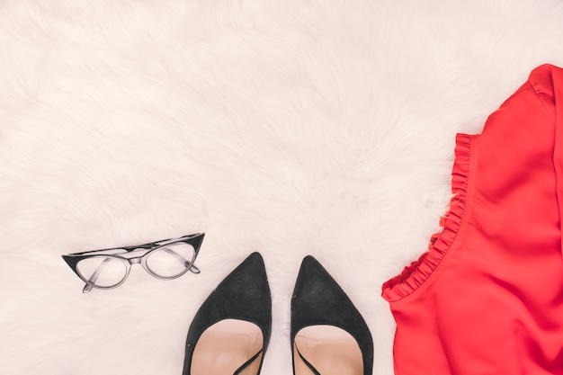 Woman shoes with skirt and glasses on blanket
