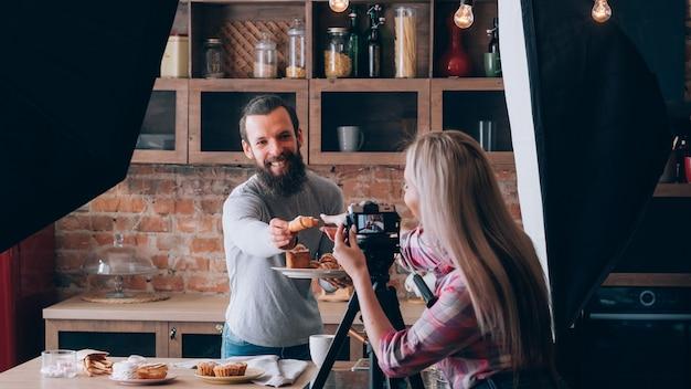여자 촬영 음식 블로거. 사진 촬영. 신선한 파이 접시와 부엌 카운터에서 남자. 치료를 받으십시오. 백 스테이지 사진.