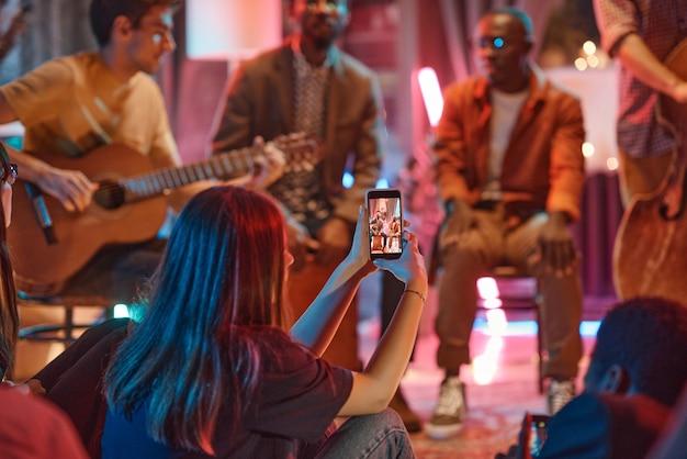 彼女の携帯電話でパフォーマンスを撮影する女性