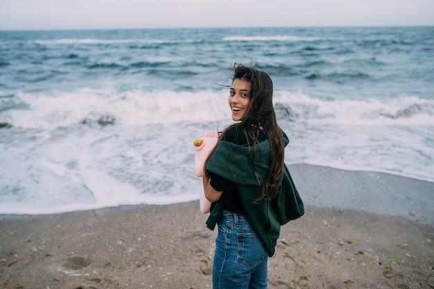 女性がスマートフォンで海の波を撃つ