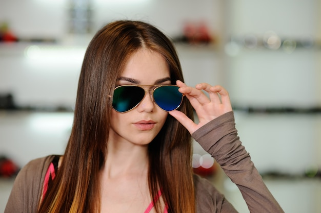 Woman in shop chooses optical glasses