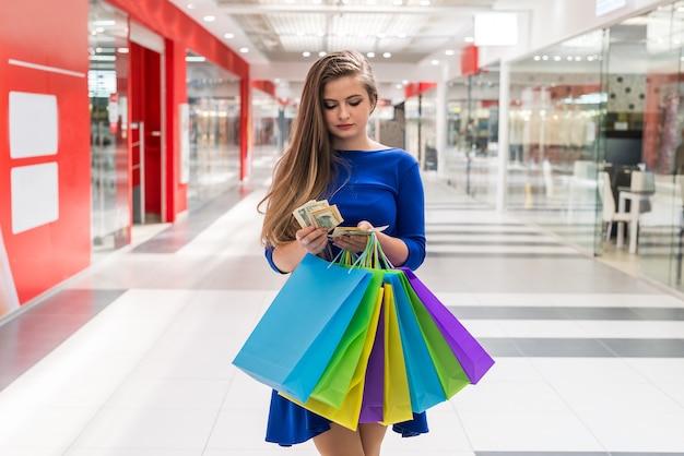 買い物中毒者が買い物のためにドル紙幣を数える