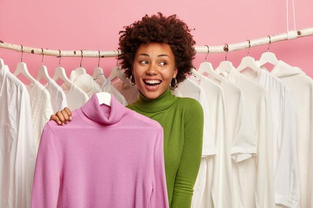 La donna maniaca dello shopping sorride ampiamente, guarda con un'espressione allegra e sognante, va a vestirsi per un appuntamento, tiene un poloneck viola pastello sul gancio