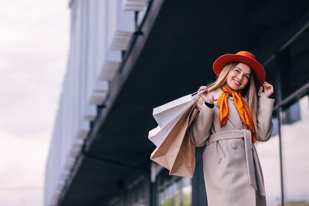 Женщина-шопоголик с бумажными пакетами для покупок гуляет по городу