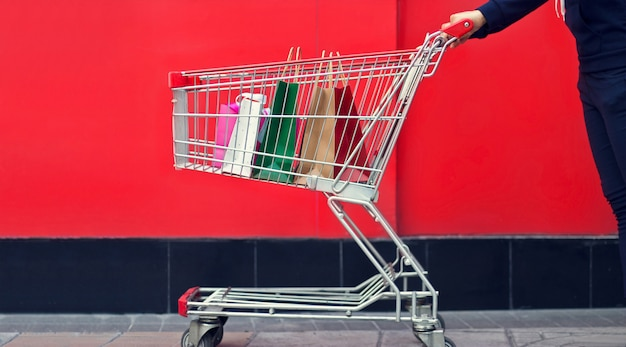 Woman shopper and shopping bag in a trolley or shopping cart on red wall the mall backgrou
