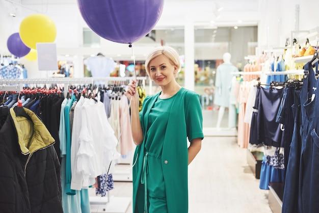 Торговая одежда женщины. покупатель смотрит на одежду в магазине. красивая кавказская женская модель.
