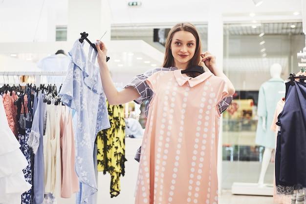 Торговая одежда женщины. покупатель смотрит на одежду в магазине. красивая счастливая улыбающаяся кавказская женская модель.
