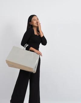 女性のショッピングのコンセプト。セールシーズン中の女の子とショッピングバッグを楽しく。店舗やオンラインショップ、白い背景から商品を購入する活動や活動中の幸せな若いアジアのタイの女性。