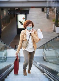 Женщина делает покупки в торговом центре с маской для лица, новый нормальный, covid-19
