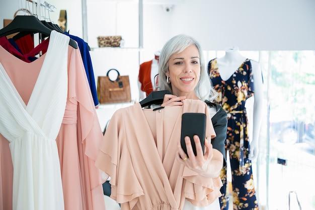 여자 패션 스토어에서 쇼핑하고 선택한 드레스를 보여주는 핸드폰에 친구를 컨설팅. 미디엄 샷. 부티크 고객 또는 커뮤니케이션 개념