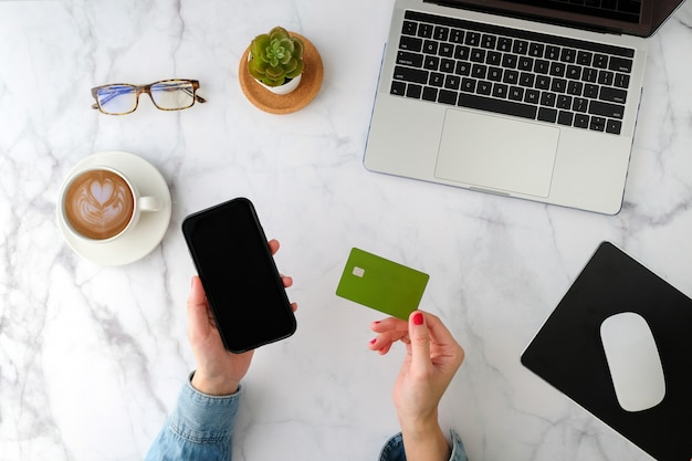 Woman shopping online on the mobile phone application with the green credit card. flat lay and modern style.