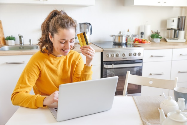 Woman shopping online and paying with gold credit card. young girl sitting with laptop buying on internet enter credit card details on kitchen indoor background.