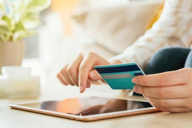 タブレットとリビングルームのクレジットカードでオンラインショッピングをしている女性。 eコマースの概念
