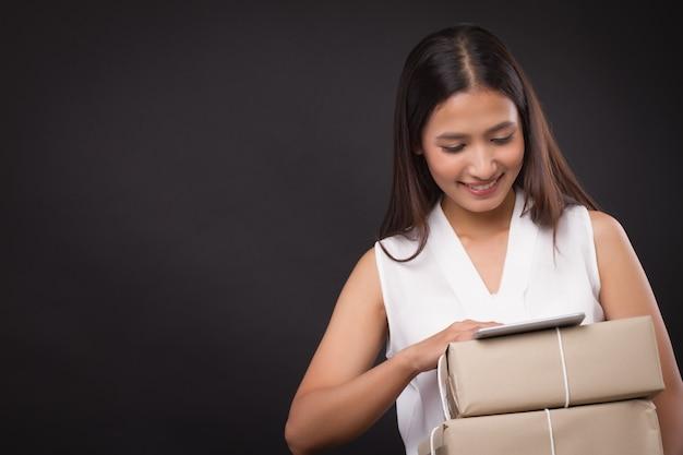 소포 배달 상자를 들고 태블릿으로 온라인 쇼핑을 하는 여성