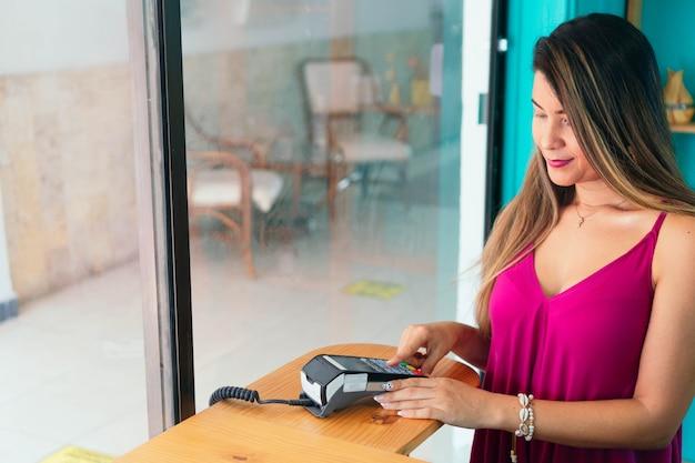 미용실에서 신용카드와 데이터폰을 사용하여 쇼핑하는 여성