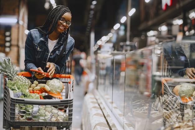 Женщина, делающая покупки овощей в супермаркете