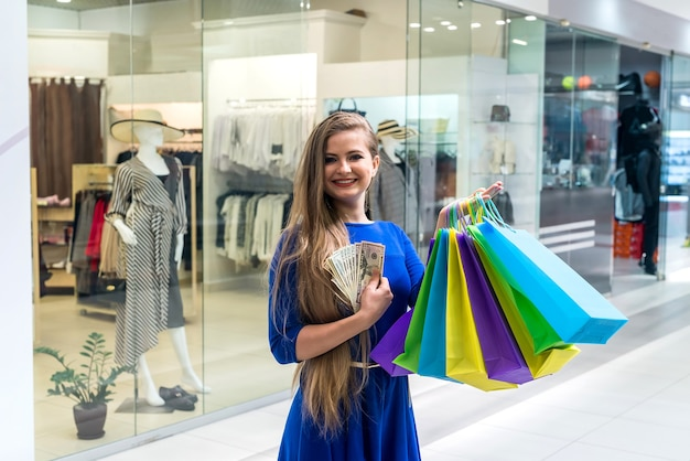 Woman on shopping with dollars and colorful bags