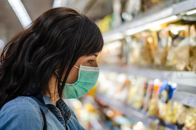 Woman shopping with a green mask in a supermarket