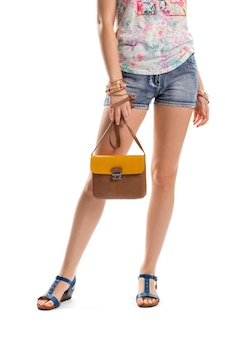 Woman in short blue shorts. bicolor handbag and blue sandals. new summer look and accessories. quality leather bag with strap.