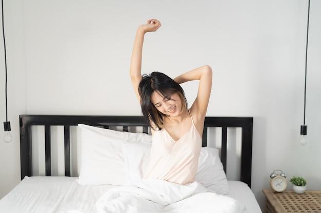 目覚めた後、ベッドで伸びる女性の短い髪、背面図